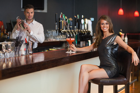 Gorgeous woman in black dress having a cocktail in a classy bar photo
