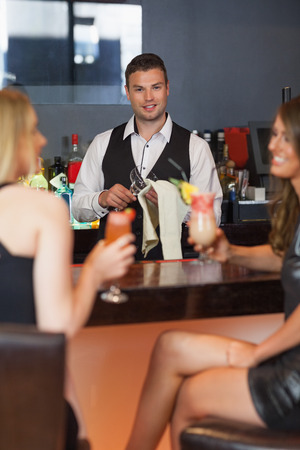 Handsome bartender working while gorgeous friends talking in a classy bar photo
