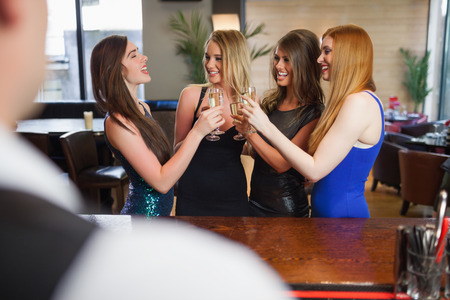 Gorgeous women clinking their flutes of champagne in a classy bar photo