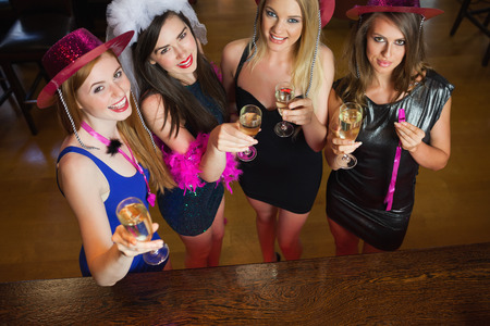 Happy gorgeous women holding flutes of champagne having hen party in a classy bar photo