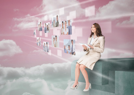 Smiling businesswoman using futuristic interface while cloud computing photo