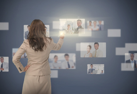 staffing: Businesswoman selecting digital interface showing coworkers Stock Photo