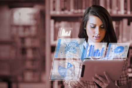 Cute student working on her futuristic tablet in a library photo