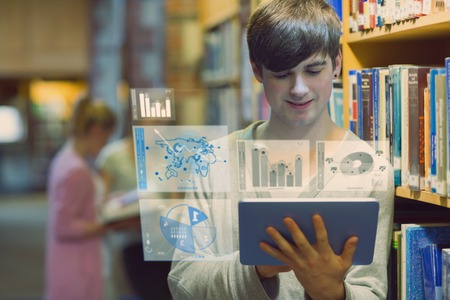 Young man studying on his digital tablet computer in a library Stock Photo - 25817633
