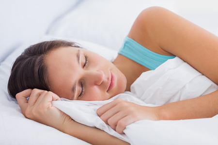 peacefully: Beautiful brunette sleeping peacefully in bed at home in the bedroom