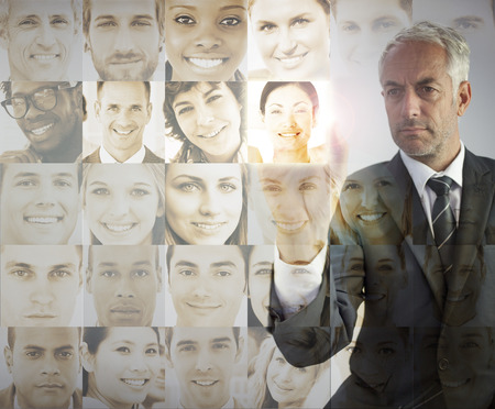Serious businessman choosing future employees on digital interfaces photo
