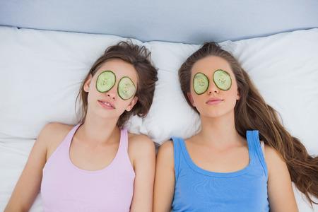 pijamada: Amigos que se relajan en la cama con el pepino en los ojos en pijamas