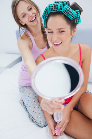 Girl wearing rollers looking in mirror and talking to friend at home on girls night in photo