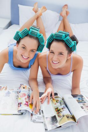 pijamada: Amigos felices en rodillos de pelo en la cama mirando y sonriendo a la c�mara en la fiesta de pijamas