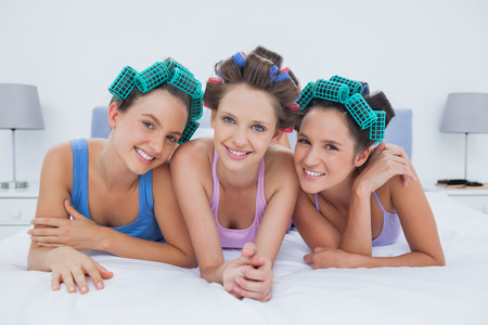 Girls in hair rollers lying in bed smiling and looking at camera at sleepover photo