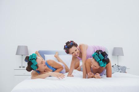 pijamada: Chicas en los rodillos del pelo que se divierte en la cama en la fiesta de pijamas