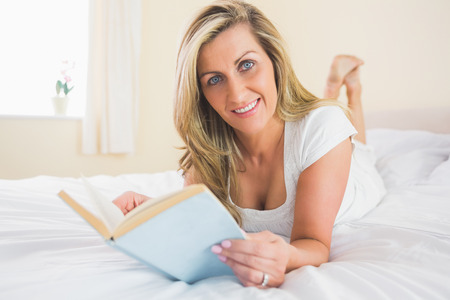 Joyful mature blonde woman looking at camera reading a book lying on her bed in a bedroom photo