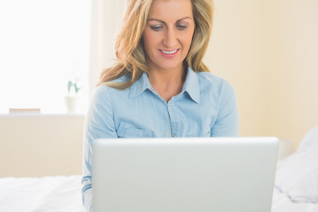 Thoughtful mature blonde woman sitting on a bed using her laptop in a bedroom photo