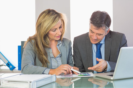 personal data assistant: Two content mature business people trying to understand figures at office