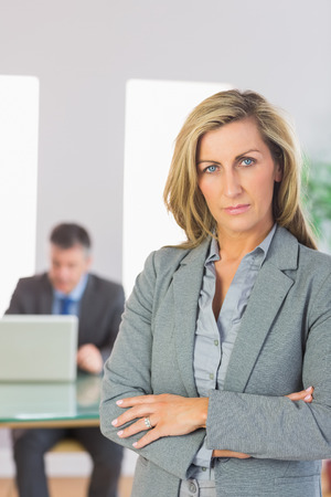 unsmiling: Serious blonde businesswoman looking at camera crossed arms with a mature businessman working on laptop on background at office  Stock Photo