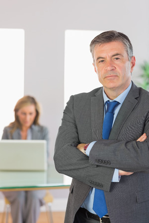 unsmiling: Irritated mature businessman looking at camera crossed arms with a blonde businesswoman working on laptop on background at office