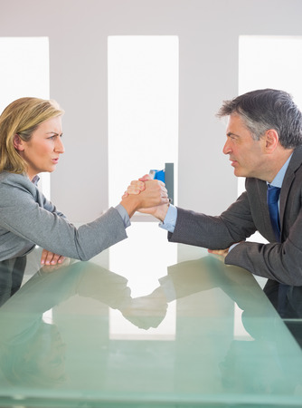 female wrestling: Two annoyed mature businesspeople having an arm wrestling sitting around a table at office Stock Photo