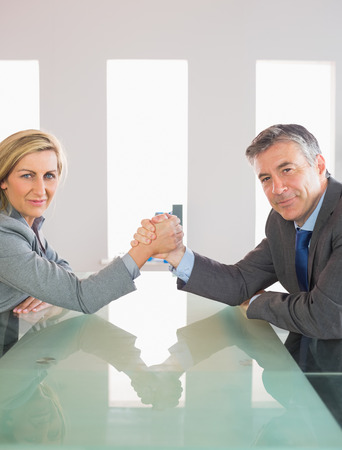 female wrestling: Two smiling mature businesspeople having a showdown sitting around a table at office Stock Photo