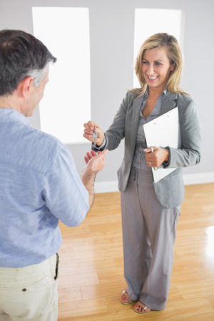Laughing blonde realtor holding a briefcase and giving a key to a mature buyer in an empty room photo