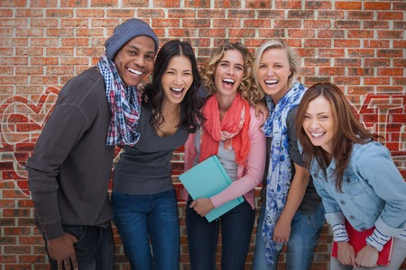 Smiling group of friends posing together on brick background photo