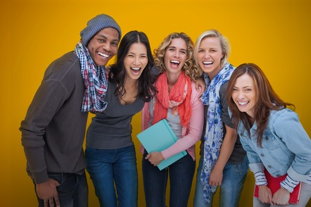 student university: Cheerful group of friends laughing together on yellow background Stock Photo