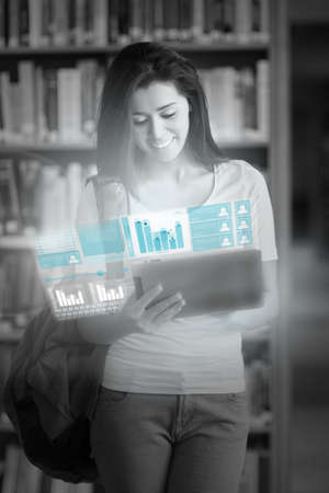 digital library: Cheerful pretty student working on her futuristic tablet in university library Stock Photo