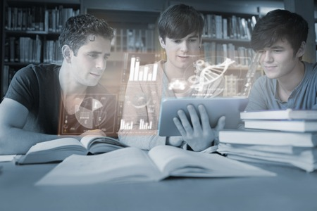 Serious young men studying medicine together with futuristic interface in university library photo