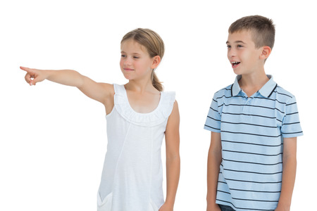 taken: Young girl showing something to her brother while posing on white background Stock Photo