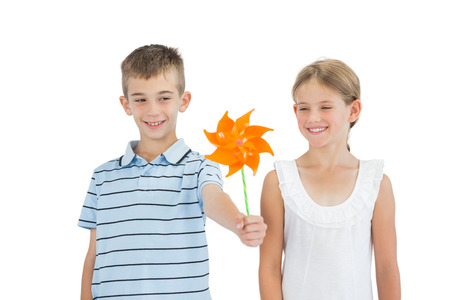 Brother and sister playing with pinwheel on white background photo