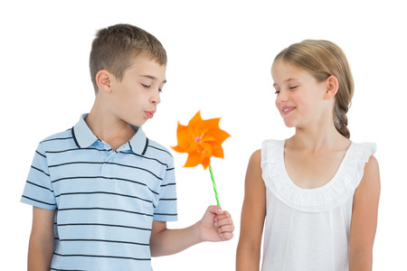 Peaceful brother and sister playing with pinwheel on white background photo