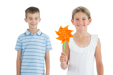 Happy brother and sister playing with pinwheel on white background photo