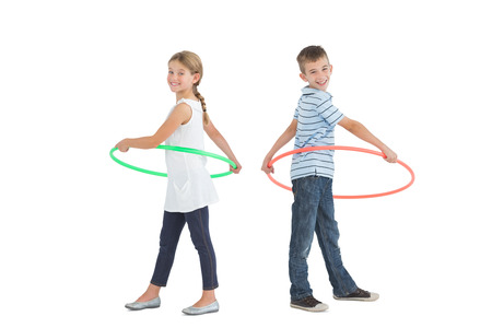 Brother and sister playing with hula hoop together on white background Stock Photo