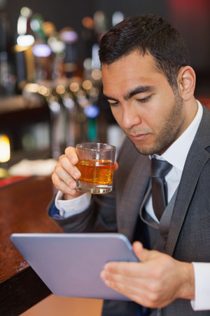 Serious businessman working on his tablet computer while having a whisky in a classy bar photo
