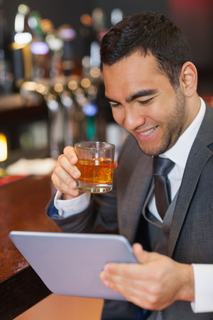 Smiling businessman working on his tablet while having a whiskey in a classy bar photo
