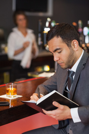 Cheerful businessman writing on his datebook in a classy bar photo