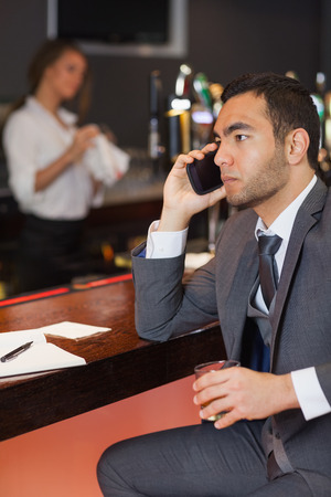 Serious businessman having a phone call in a classy bar photo