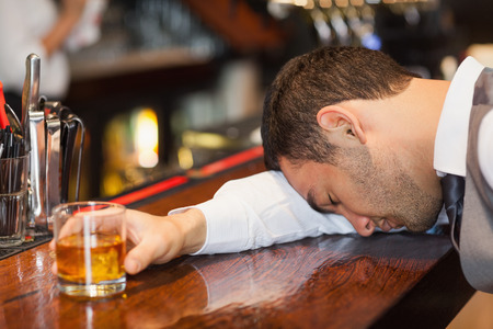 Drunk businessman lying on a counter in a classy bar photo