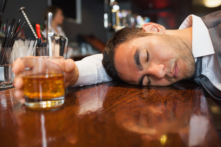 Drunk and unconscious businessman lying on a counter in a classy bar photo