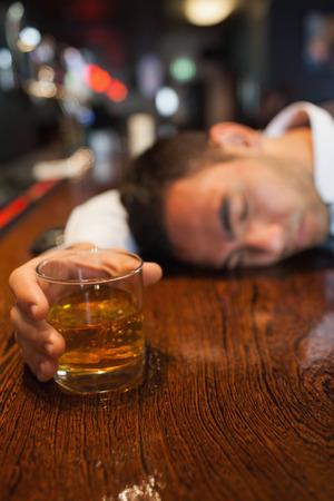 Drunk businessman holding whiskey lying on a counter in a classy bar photo
