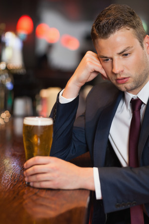 Pensive businessman having a drink in a classy bar photo
