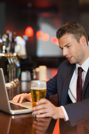 Businessman having a drink while working on his laptop in a classy bar photo