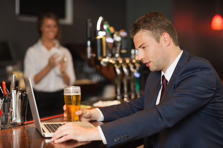Businessman having a beer while working on his laptop in a classy bar photo