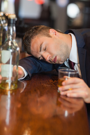 inebriated: Drunk businessman holding whiskey glass lying on a counter in a classy bar