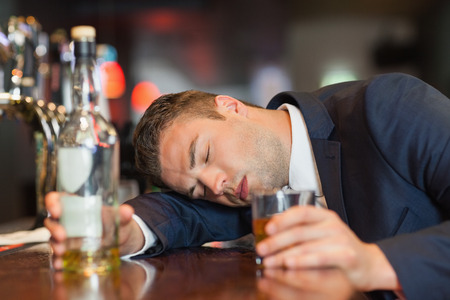 Unconscious businessman holding whiskey glass lying on a counter in a classy bar photo