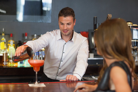 Handsome bartender serving cocktail to gorgeous woman in a classy bar photo