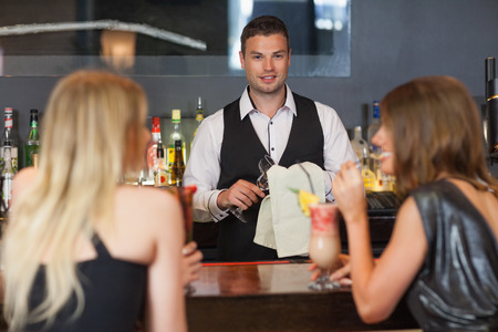 Handsome bartender working while gorgeous women talking on the counter in a classy bar photo