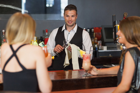 Handsome bartender working while gorgeous friends speaking in a classy bar photo