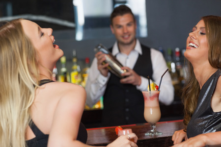 Handsome bartender working while gorgeous friends laughing in a classy bar photo