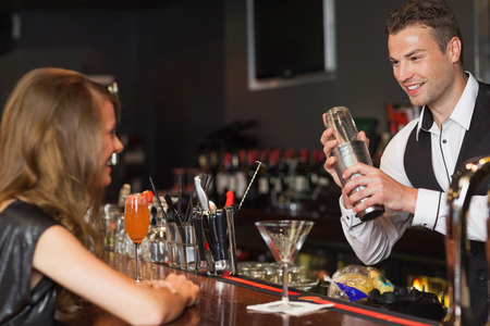 Handsome bartender serving cocktail to beautiful woman in a classy bar photo