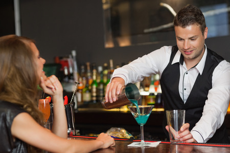 Handsome bartender serving cocktail to attractive woman in a classy bar photo